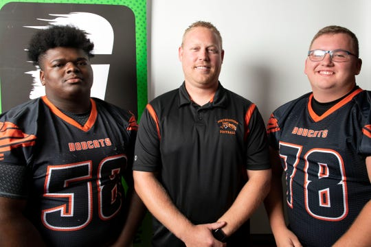 Northeastern's Kelvin Brown, from left, head coach Jon Scepanski and Stephen Gundy pose for a photo during YAIAA football media day in Hanover on Thursday, August 2, 2018.