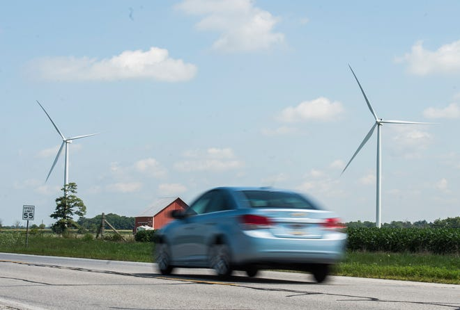 A vehicle passes by wind turbines along U.S. 27 in Randolph County on Thursday, Aug. 2, 2018.