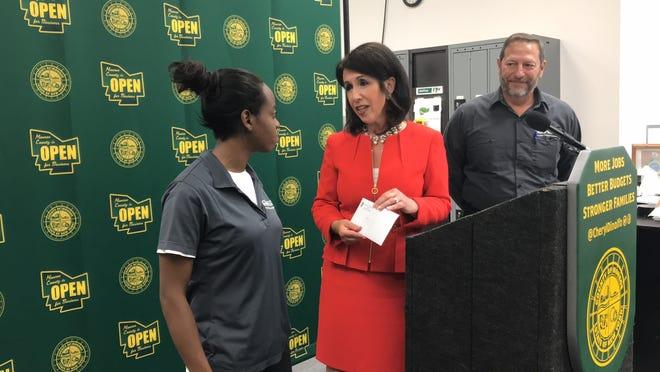 Monroe County Executive Cheryl Dinolfo (C) presents Niayah Blair (L) and Lou Romano (R) checks for $1,500 a bonus for completing the program.