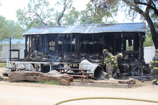 Firefighters work to clean up a cabin that burned on Aug. 2, 2018 at Spring Creek Marina.