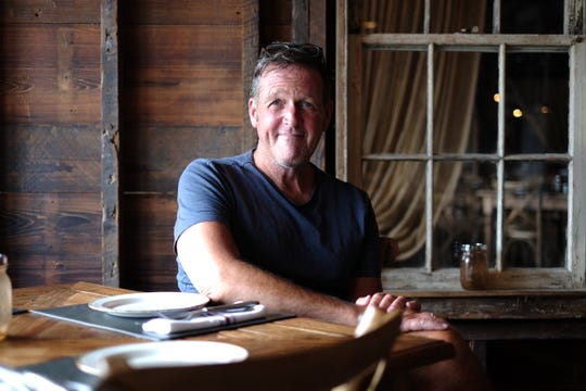 John Trader sits at a table in his cozy Fenwick Island restaurant Our Harvest
