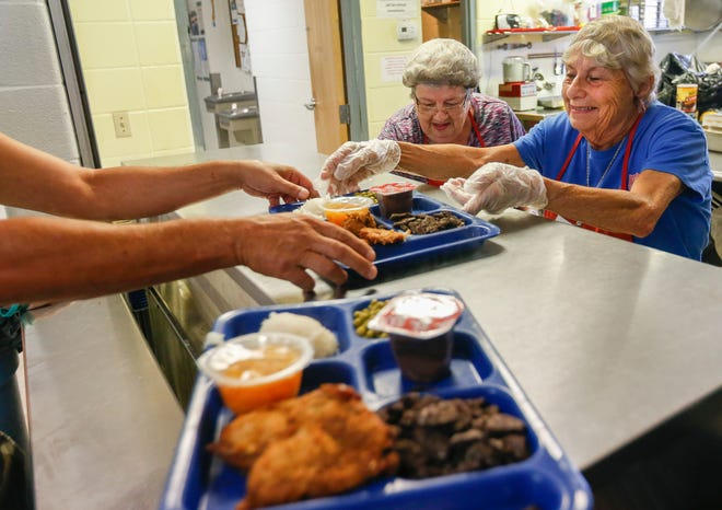 Volunteers Dorothy Cutler, right, and Carolyn Childress serve lunch at the Salvation Army's Harbor House on Thursday, Aug. 2, 2018.