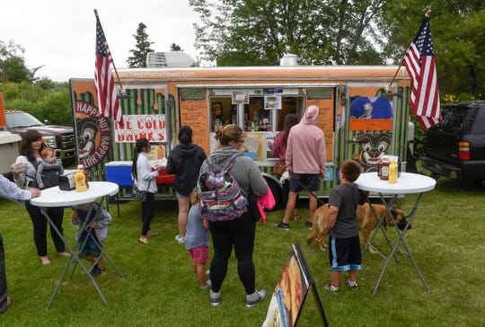 People place their orders at the Happy Hut truck during Summertime by George! Wednesday, Aug. 1, in St. Cloud.