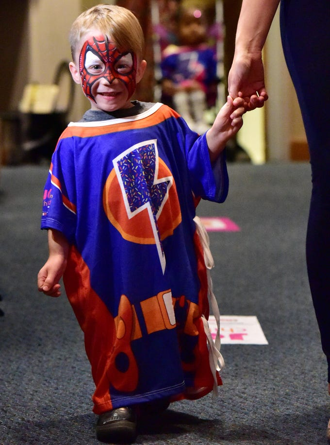 West Glenn, 5, walks down an isle during a Superhero Kids' Fashion Show held by the Dunkin' Donuts Joy in Childhood Foundation at Greenville Memorial Hospital on Thursday, August 2, 2018.