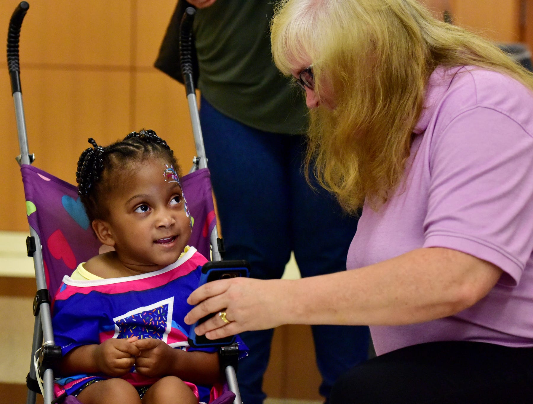 Novah Mac, 4, is shown a picture of herself during a Superhero Kids' Fashion Show held by the Dunkin' Donuts Joy in Childhood Foundation at Greenville Memorial Hospital on Thursday, August 2, 2018.