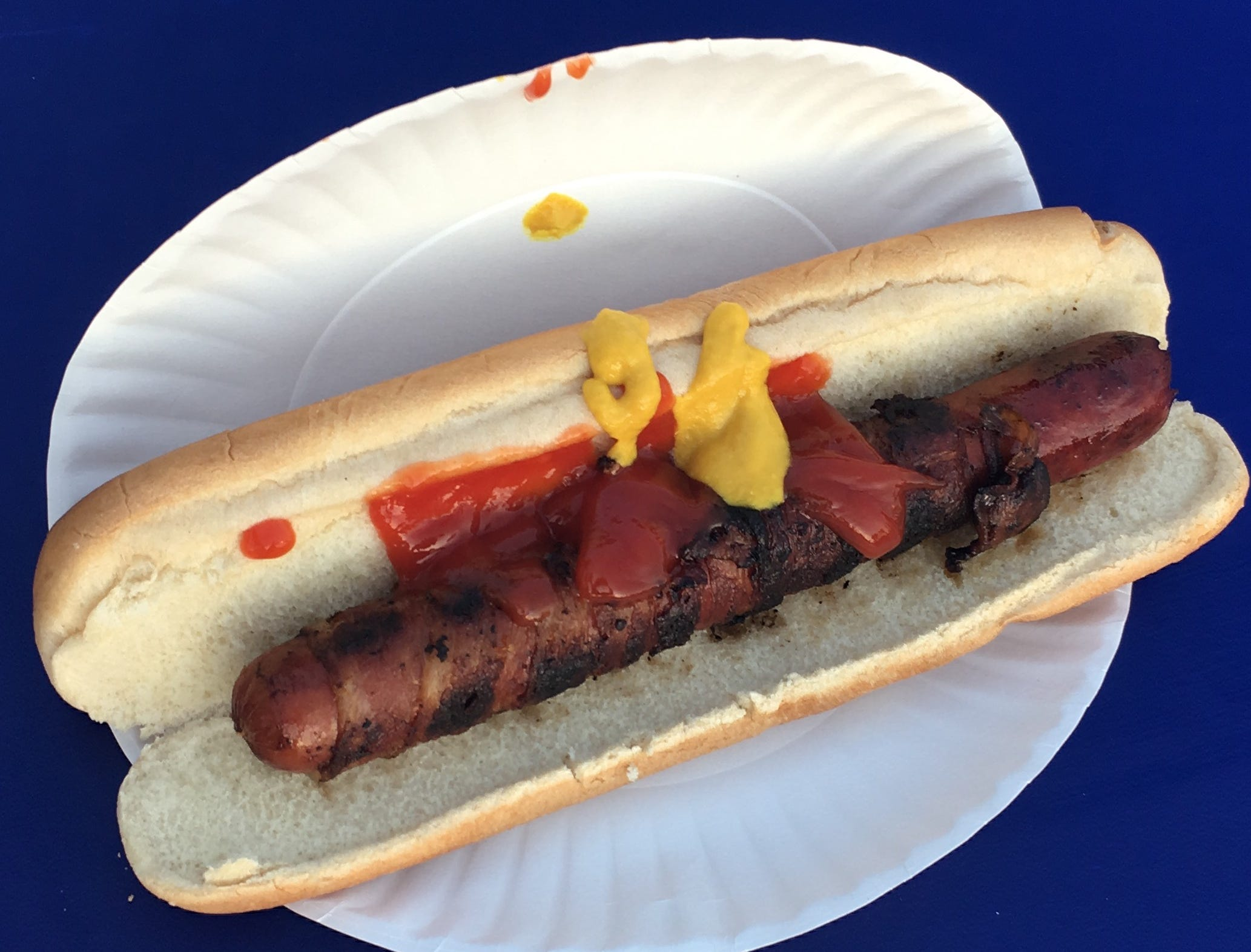 Bacon-wrapped kosher hot dog on a white bun, topped with ketchup and mustard.
