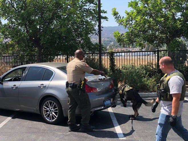 Ventura County Sheriff's deputies with a K-9 search a car suspected to be used in a Thousand Oaks burglary Wednesday.