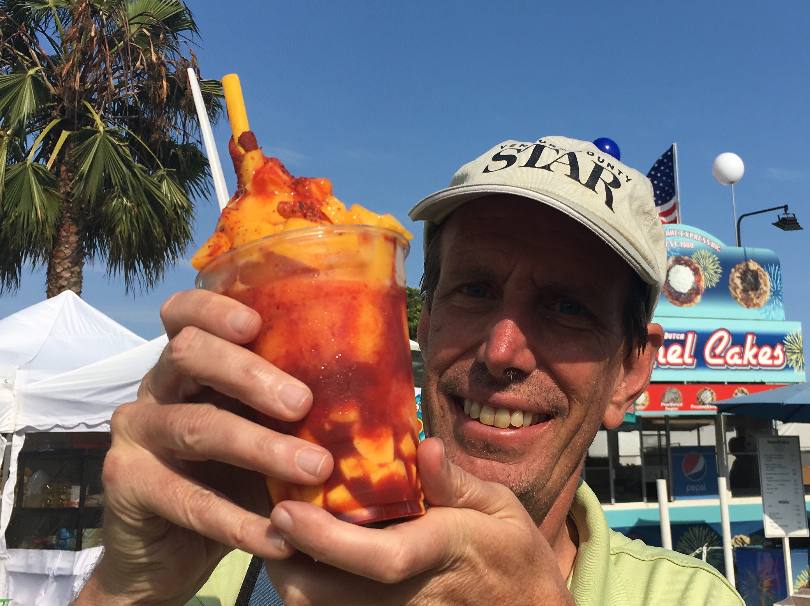 A Mangonada with a huge scoop of sorbet covered with chunks of mango and flavored with sweet, spicy chamoy sauce. It includes a big yellow straw coated with chili seasoning.