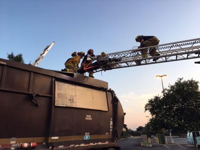 Visalia firefighters rescue a man inside a Visalia garbage truck on Thursday, Aug. 2, 2018.