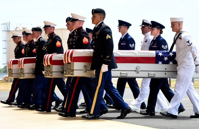 Military members carry the remains believed to be of American service members who fell in the Korean War. North Korea handed over the remains last week.