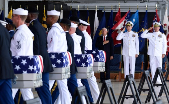 Vice President Mike Pence, Commander of U.S. Indo-Pacific Command Adm. Phil Davidson, center, and Rear Adm. Jon Kreitz, deputy director of the POW/MIA Accounting Agency, watch as military members carry transfer cases of the remains believed to be of American service members who fell in the Korean War.