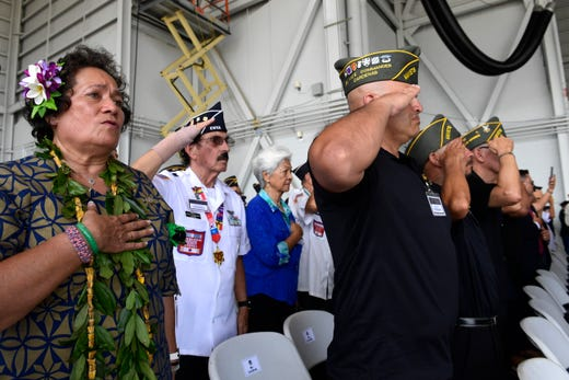 Audience members stand during the National Anthem at a ceremony marking the arrival of the remains believed to be of American service members who fell in the Korean War at Joint Base Pearl Harbor-Hickam, Hawaii, on Aug. 1, 2018.