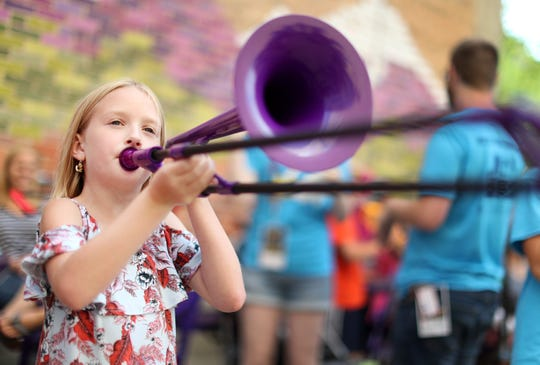 Danica Lafave, 9, plays a pBone at the pBone Jam music education event during the second day of Mile of Music Friday.