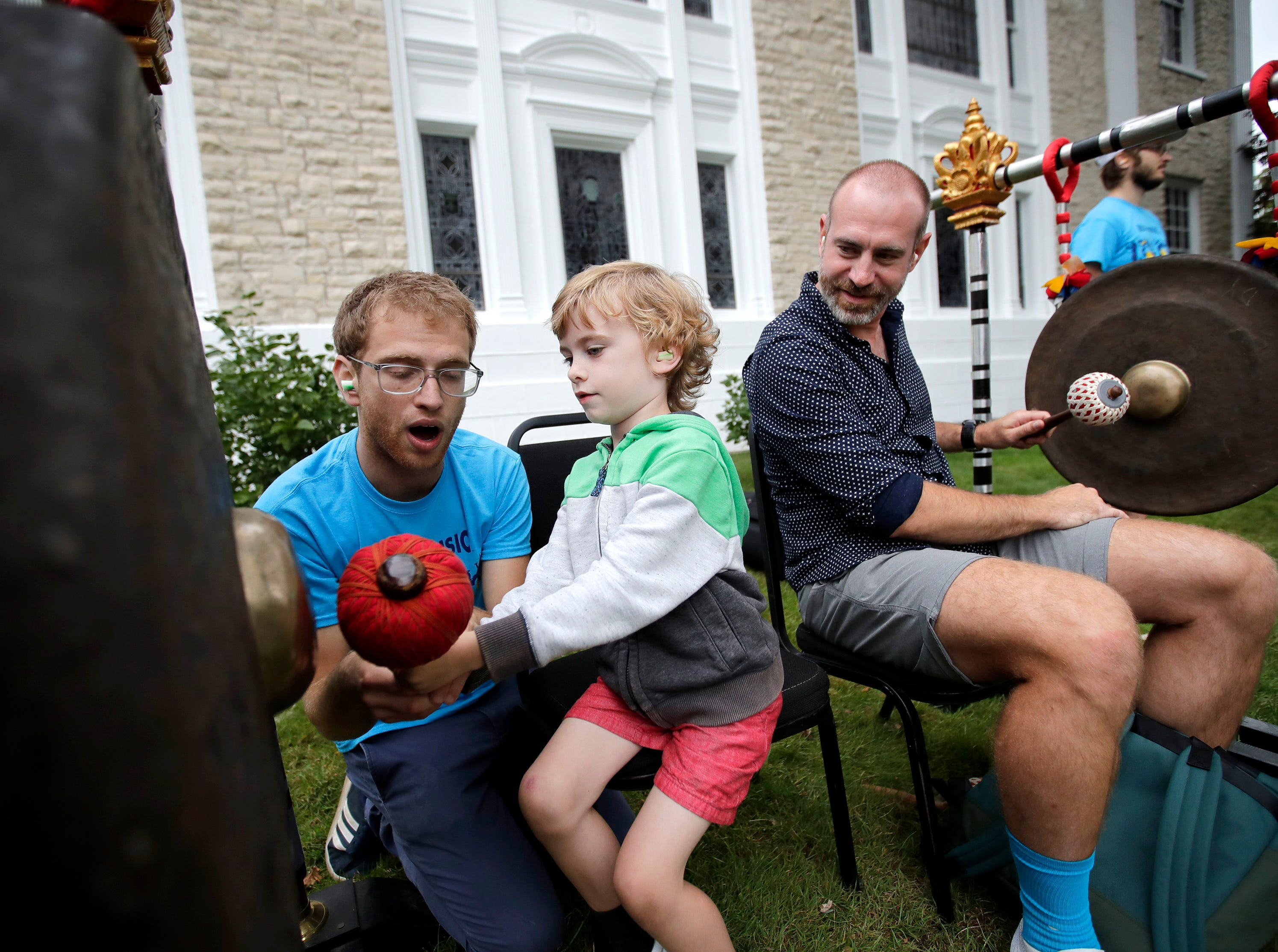 Ilan Blanck, with the music education team, helps Benji Brozek, 6, play a gong with his father Jason at the Balinese Gamelan music education workshop during the first day of Mile of Music Thursday, Aug. 2, 2018, in Appleton, Wis.Danny Damiani/USA TODAY NETWORK-Wisconsin