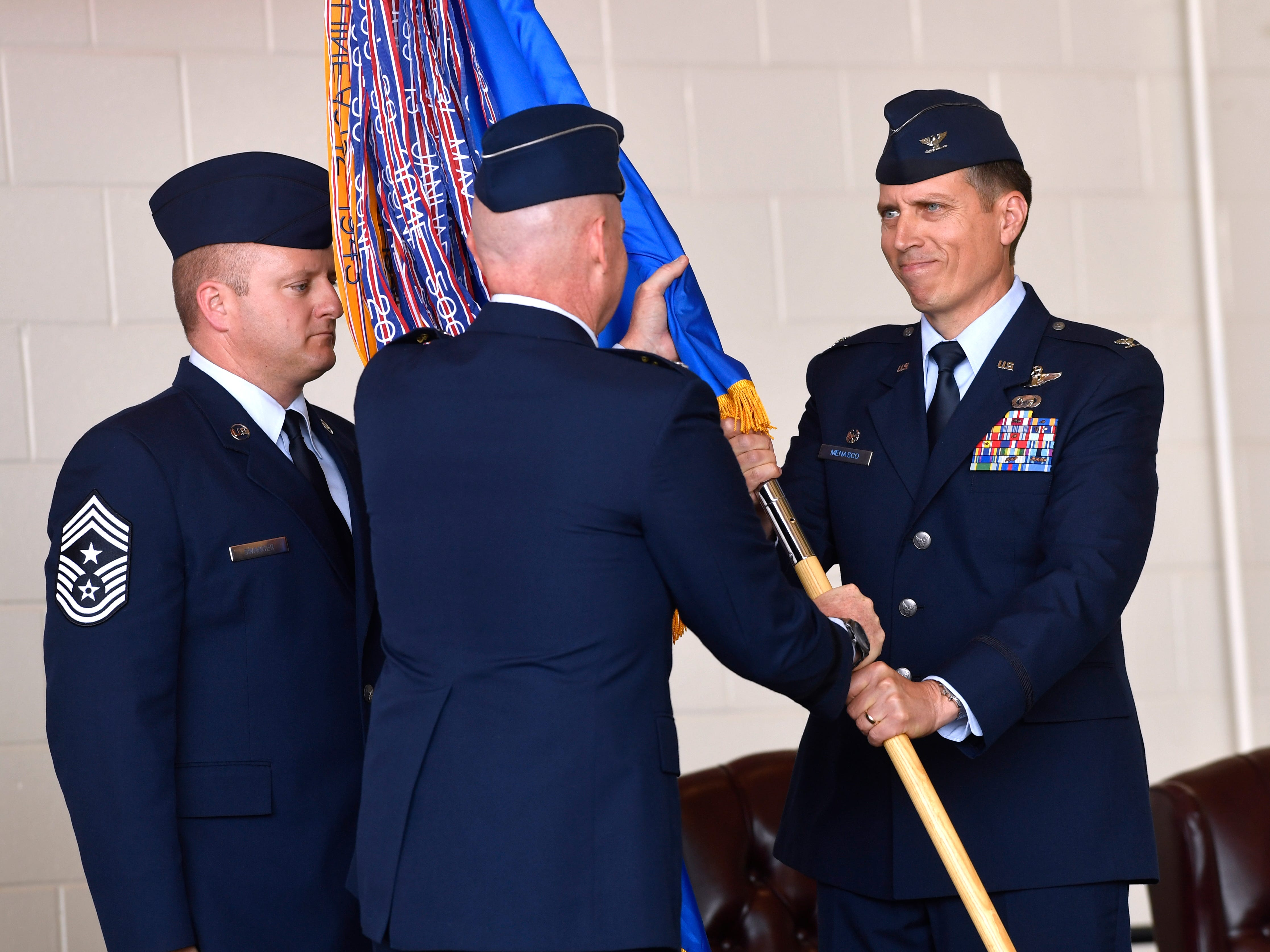 Col. Jeffrey Menasco is given command of the 317th Airlift Wing by Major Gen. Sam Barrett, Commander of the 18th Air Force, during an assumption of command ceremony Friday August 3, 2018 at Dyess Air Force Base. The passing of the guidon symbolizes the awarding of responsibility, and Mensasco handed the banners back to Command Chief Msgt. Joshua Swanger for keeping upon accepting command.