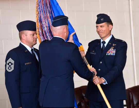 Col. Jeffrey Menasco is given command of the 317th Airlift Wing by Maj. Gen. Sam Barrett, commander of the 18th Air Force, during a ceremony Friday at Dyess Air Force Base. The passing of the guidon symbolizes the awarding of responsibility, and Mensasco handed the banners back to Command Chief MSgt. Joshua Swanger for keeping upon accepting command.  Caption Override