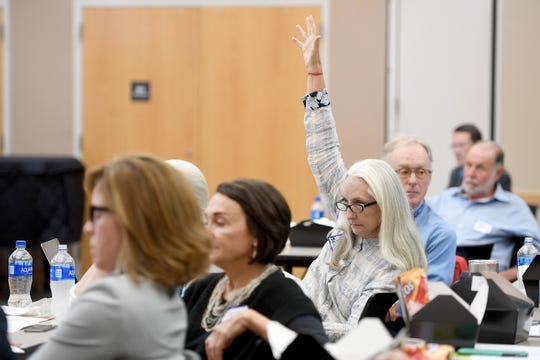 Victoria Hicks raises her hand during the WNC Conversion Health Foundation Forum at UNC Asheville on Friday, Aug. 3, 2018. The symposium focused on the Dogwood Health Trust, the successor foundation formed from the proceeds of the proposed sale of Mission Health to HCA Healthcare.