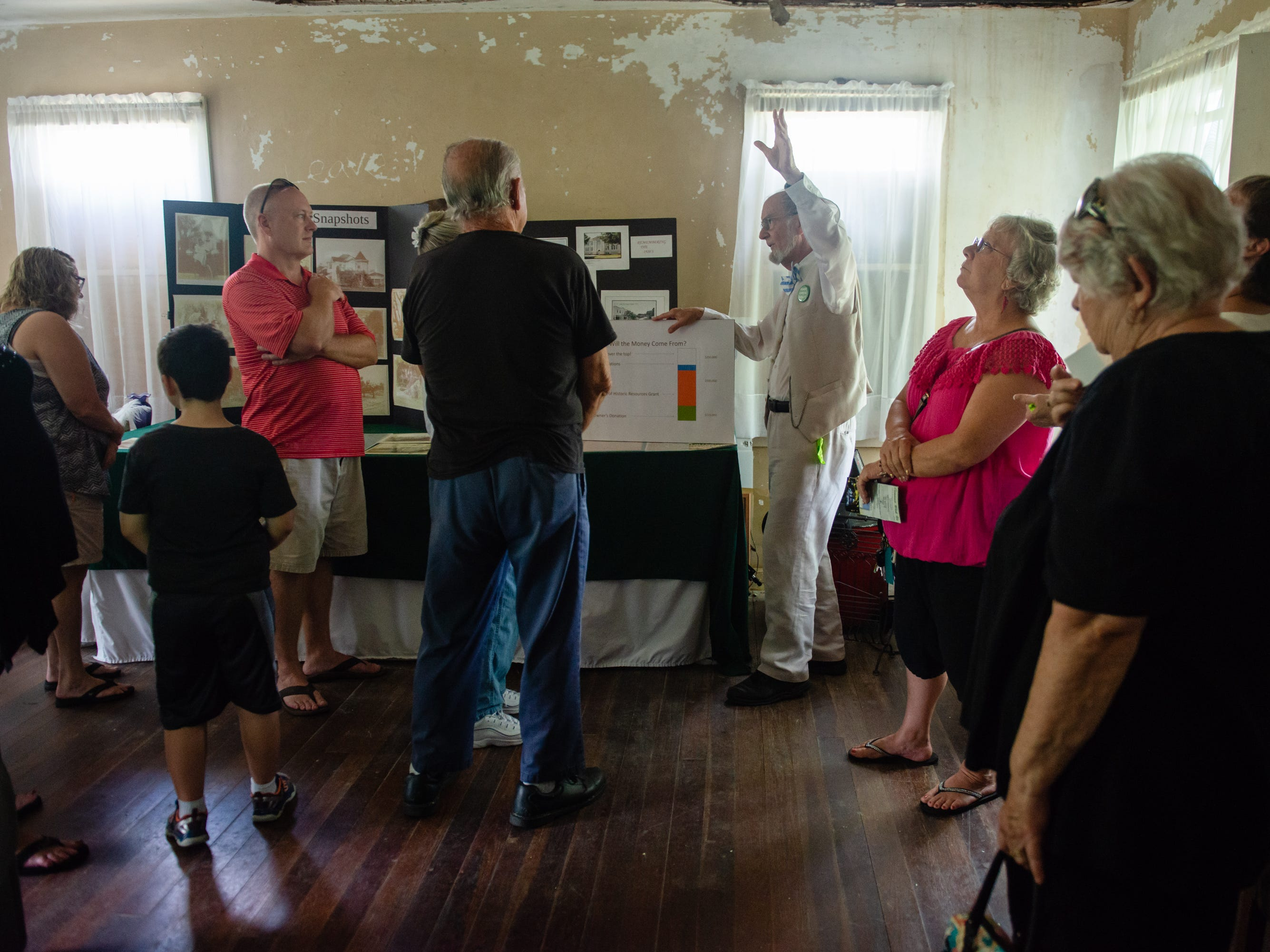 John Daly, president of Green Gables at Historic Riverview Village, Inc., talks to visitors at the Christmas in July event, which raised money to restore the Green Gables Victorian house in Melbourne.