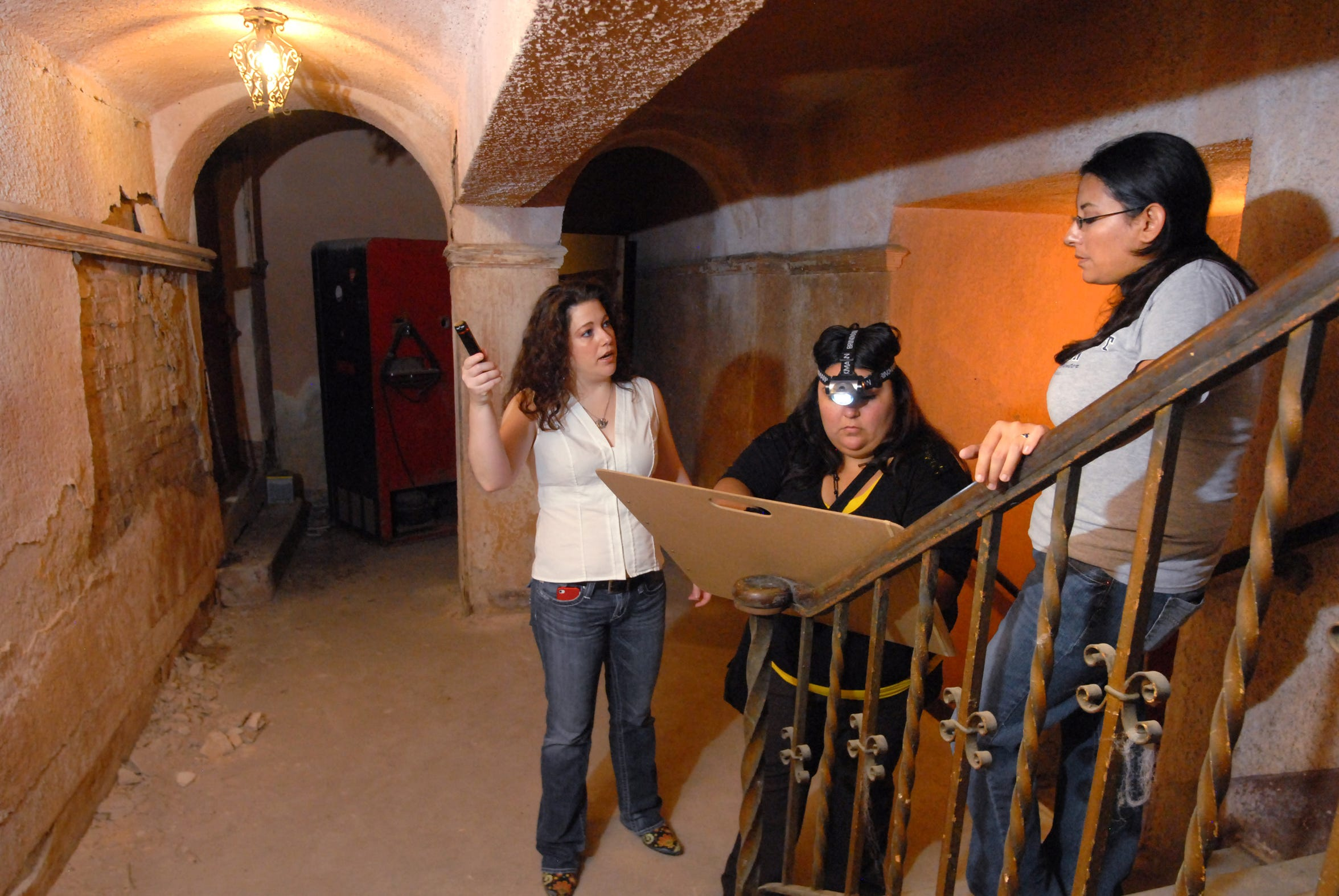 Del Mar College Professor Laura Bennett (left) with drafting students Marlina Falcon (middle) and Celeste Gonzales (right) as they talk about measuring another area of the theater to document the layout and architectural significance of the Ritz Theater in March 2012, to create a 3-D model on the computer for the nonprofit working to restore the theater to its glory days.