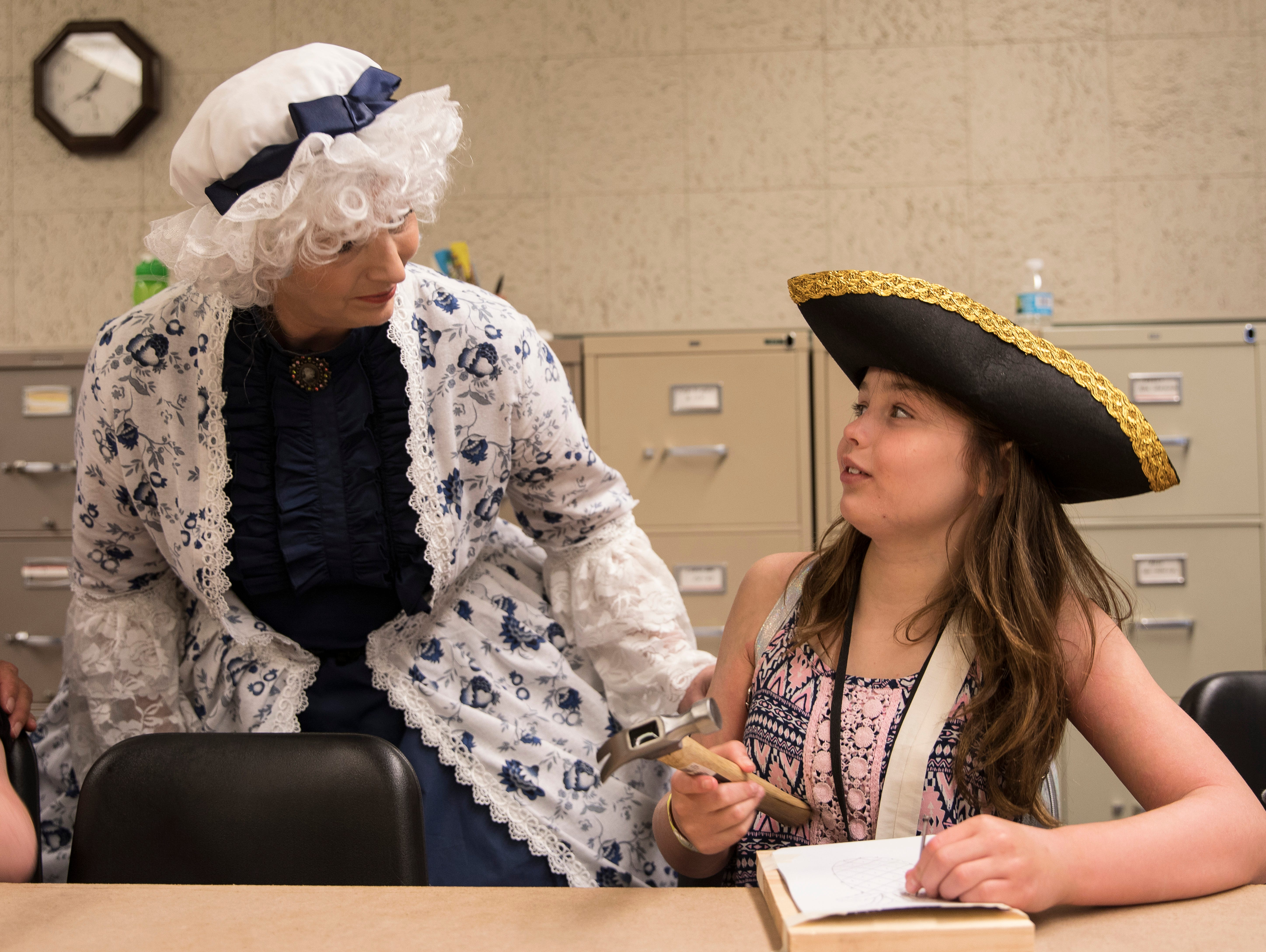 Martha Washington, portrayed by Virginia Quinn, talks to Addy Gibson about her Revolutionary War punched tin craft Wednesday during Liberty Camp.