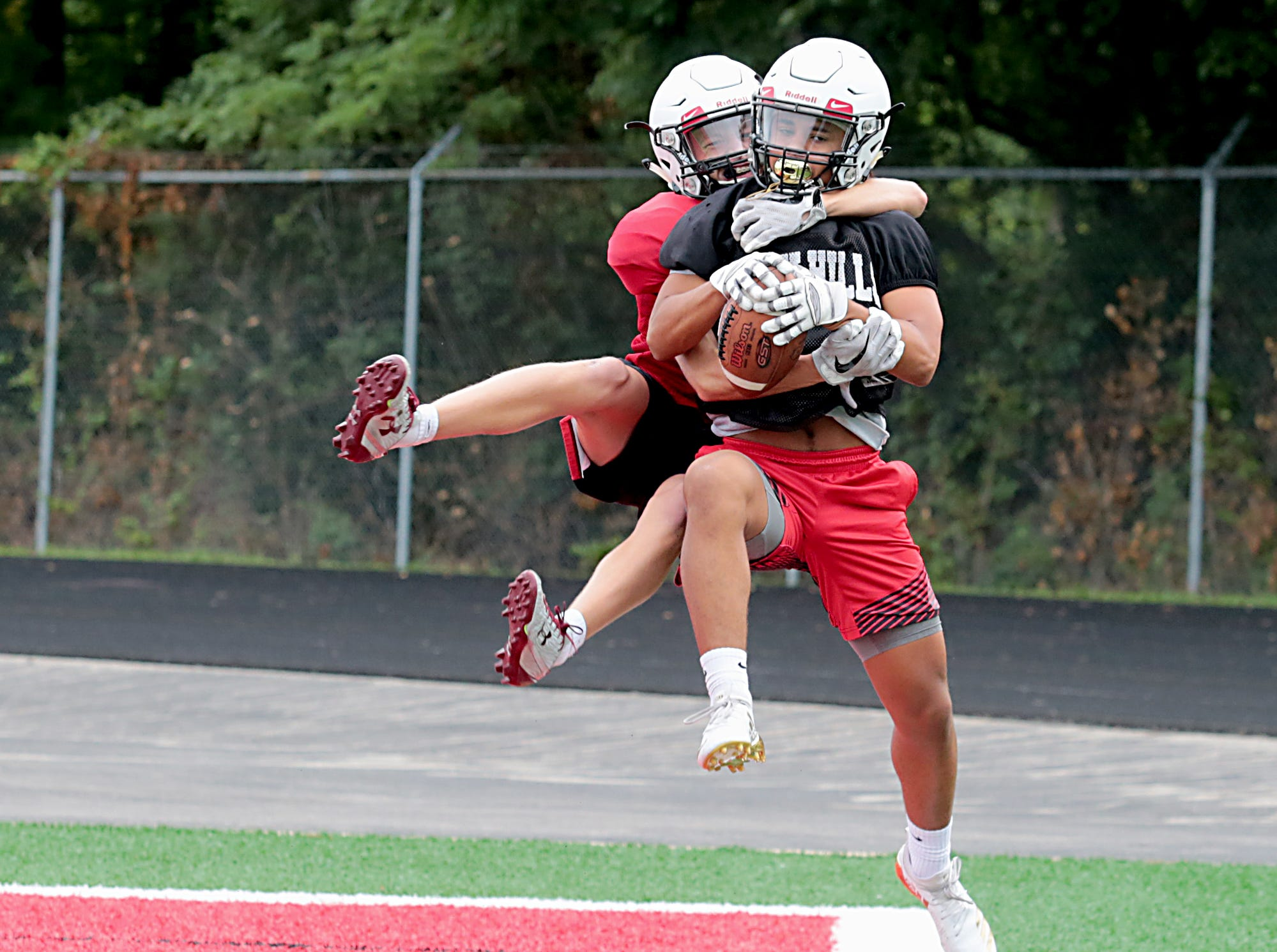 Sander Vest intercepts a pass meant for Brandon Tirey during Oak Hills football practice Wednesday, Aug. 1, 2018.