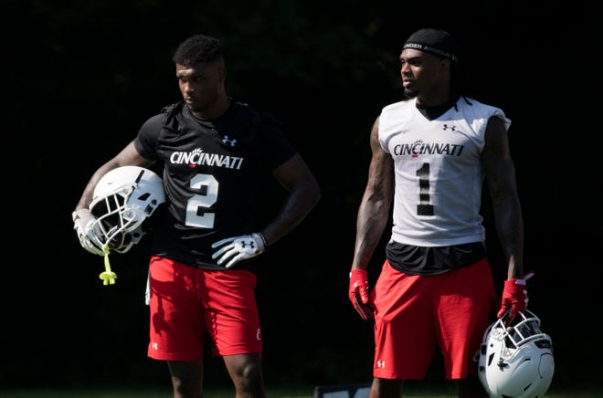 Cincinnati Bearcats senior wide receiver Kahlil Lewis (1) and senior cornerback Tyrell Gilbert (2) take a break during a recent UC practice at Camp Higher Ground in West Harrison, Indiana. Lewis is UC's top returning receiver, with 61 catches last year.