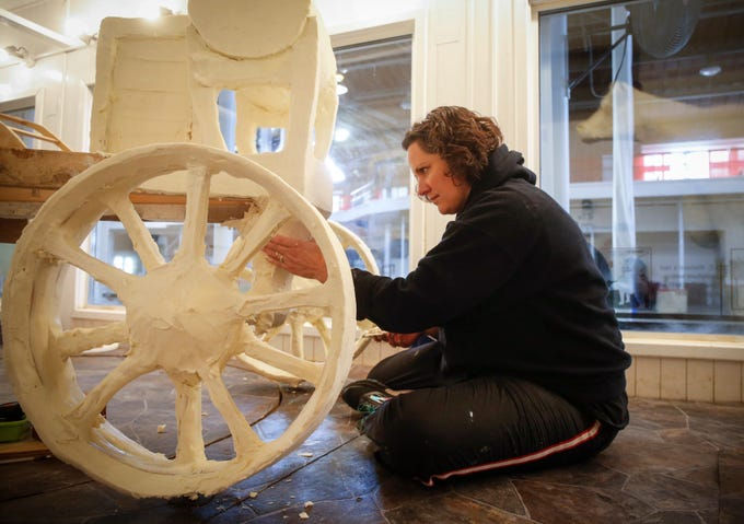 Butter sculptor Sarah Pratt of West Des Moines works on the axle of her 1918 John Deere Waterloo Boy tractor sculpture on Friday, Aug. 3, 2018, at the Iowa State Fairgrounds in Des Moines.