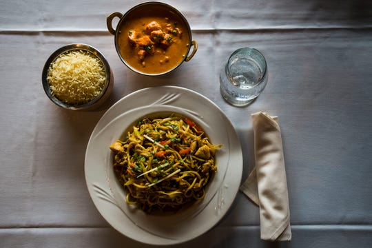 Entrées of Tibetan noodles and chicken tikka masala sit on a clean white tablecloth on Friday, Aug. 3, 2018, at Himalayan Bistro in Fort Collins, Colo.