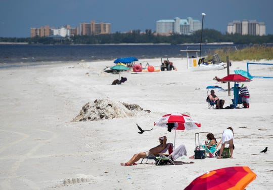 A few people braved the effects of red tide to relax on the beach on Friday morning. A pile of sand and organic material sits near sunbathers.