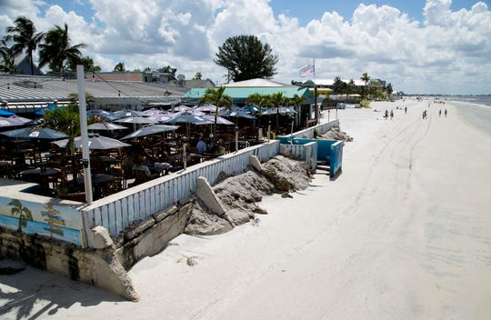 A few table of diners eat lunch at The Pierside Grill on Fort Myers Beach. Red tide and its effects have driven diners away from Fort Myers Beach.