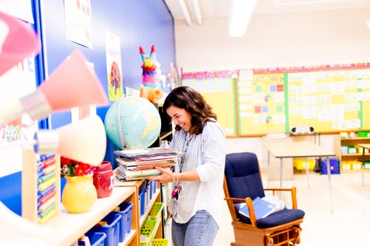 Kindergarten teacher Patricia Galicki organizes a stack of books in her room at Sam E. Hill Primary School in the Lonsdale community in Knoxville on Friday, Aug. 3, 2018.