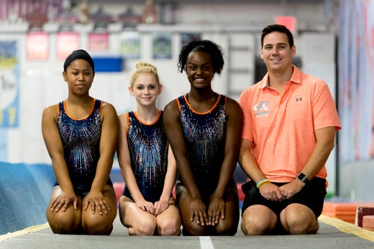 From left, Ayanna Albright, Savanna Cecil, Tia Taylor and coach Eric Thomas pose for a photo during practice at Premiere Athletics in Knoxville, Tennessee on Friday, July 27, 2018. Tia Taylor, Savanna Cecil and Ayanna Albright will represent Team USA at WAGS in St. Petersburg Russia in November.