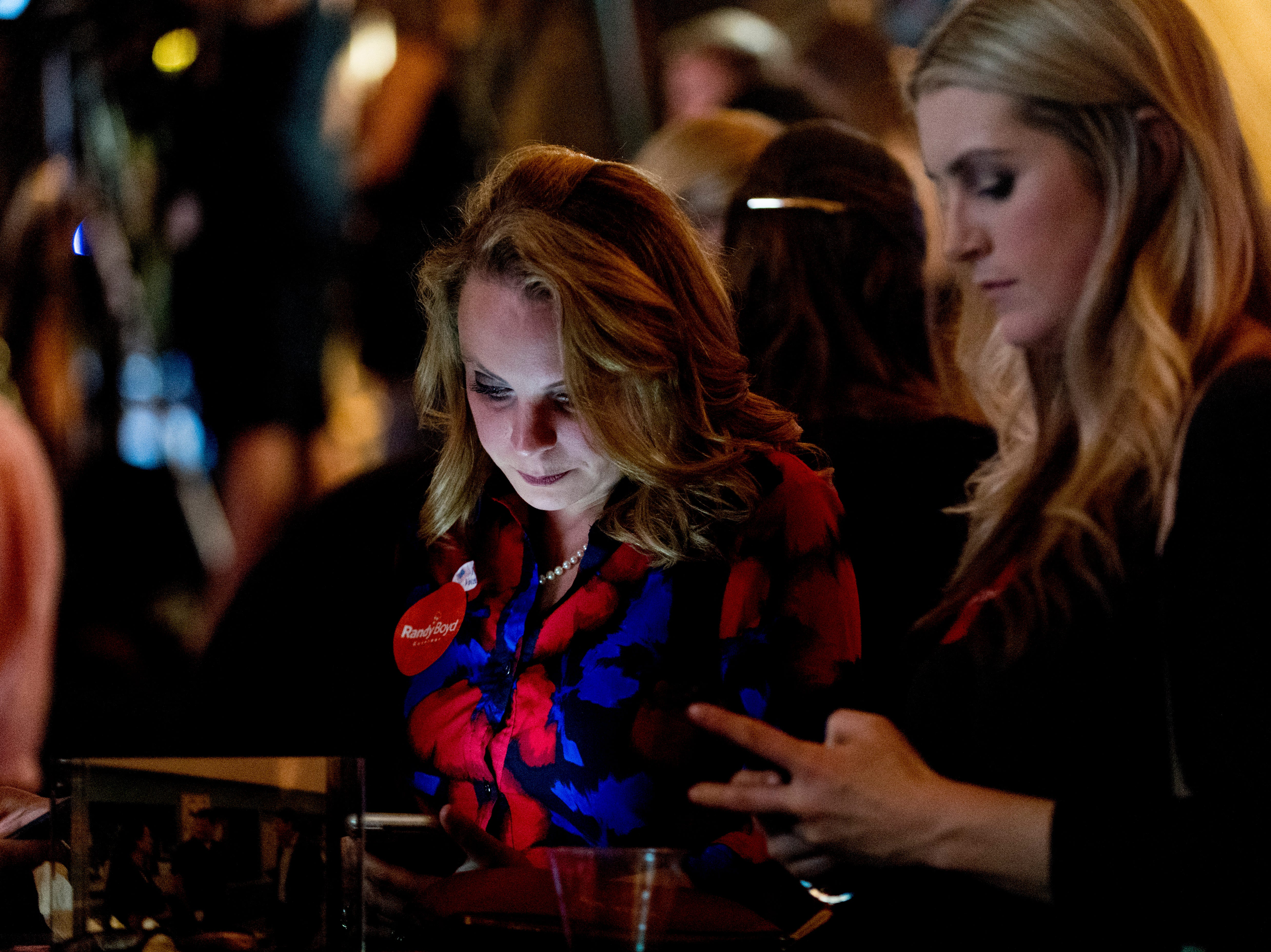 Liz Burelson, left, and Alexis Bell, of Nashville, watch the poll numbers on their phones at the Randy Boyd for Governor watch party at Jackson Terminal in Knoxville, Tennessee on Thursday, August 2, 2018.
