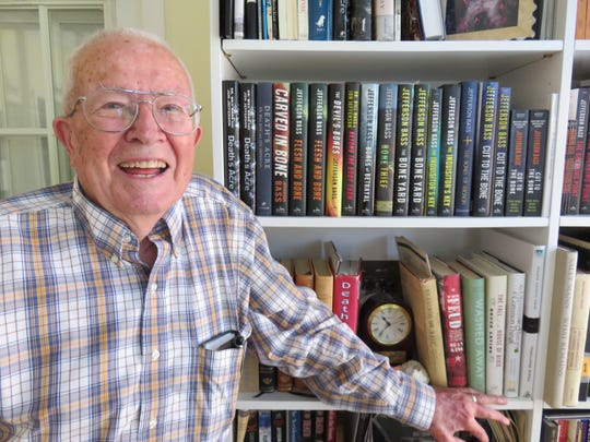 Dr. Bill Bass stands next to some of his books in his library at his West Knoxville home on July 26.