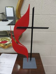 """A replica of the United Methodist Church's """"cross and flame"""" symbol stands inside the church."""