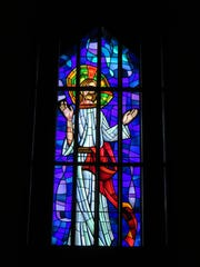 A stained-glass window stands in the rear of First United Methodist's sanctuary.