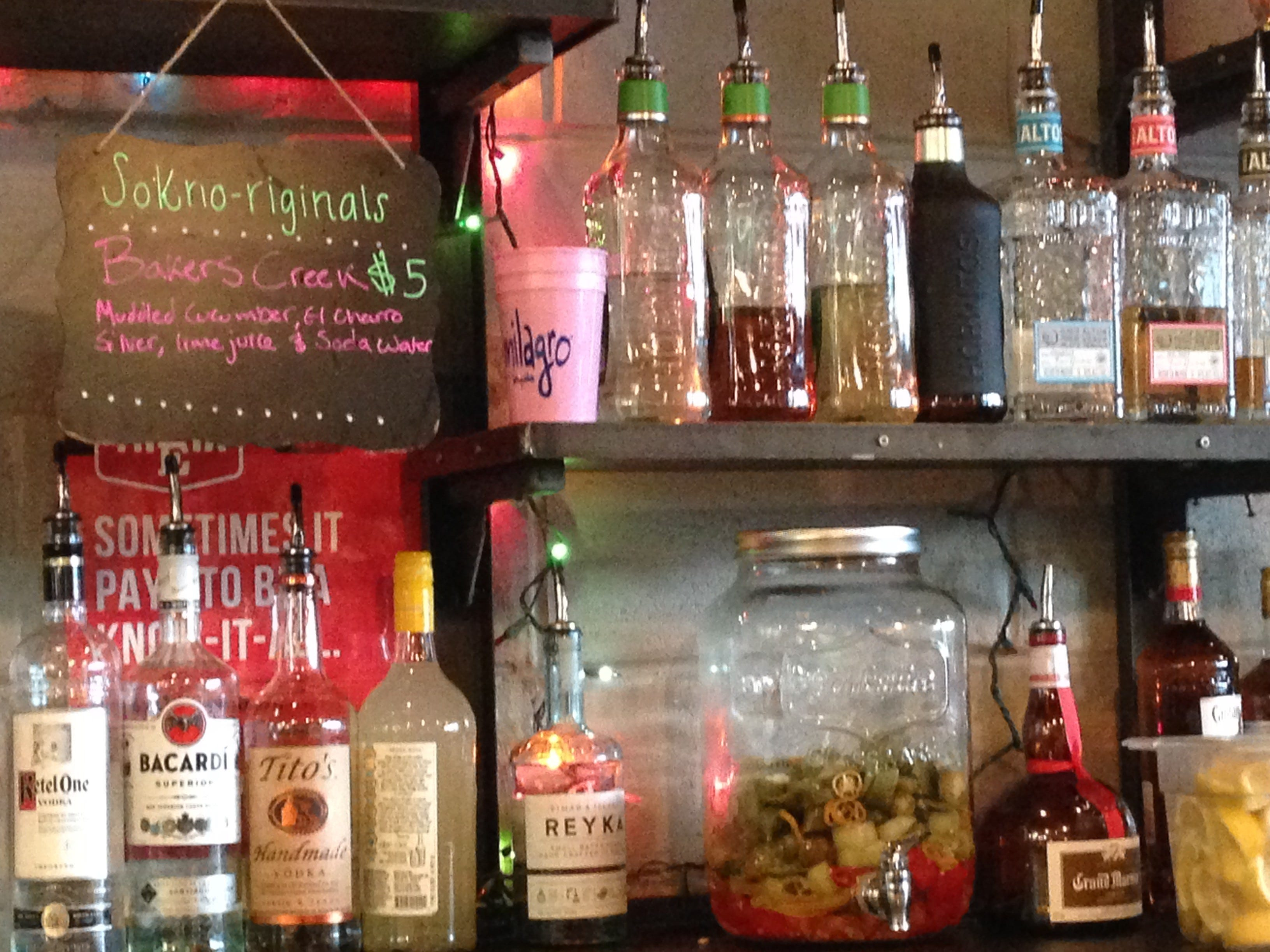 The large glass jar of infused pepper tequila is placed in the middle of the tequila section at SoKno Taco Cantina.