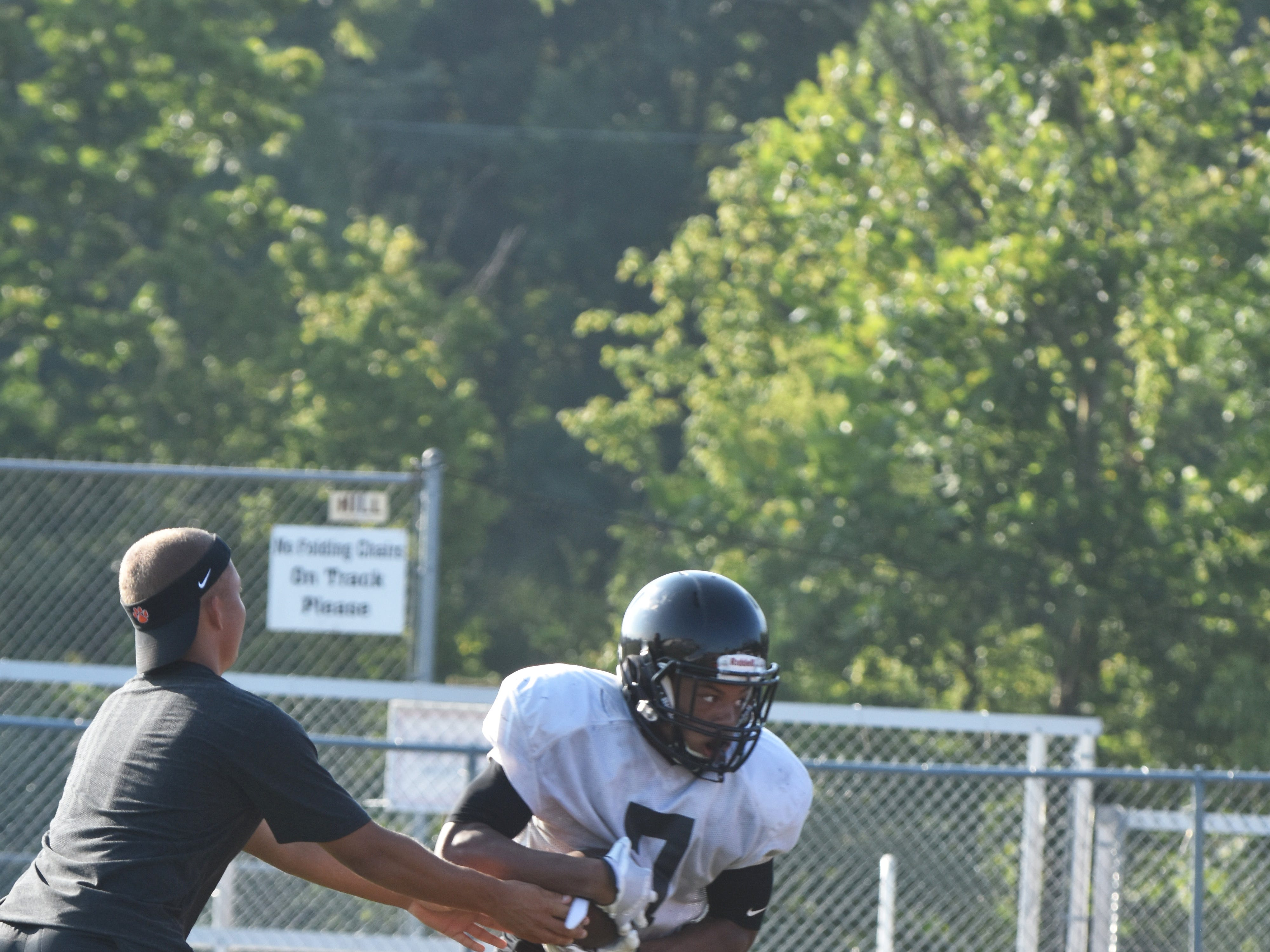Powell football player Jordan Brown takes the hand off and heads down field during a recent practice session.