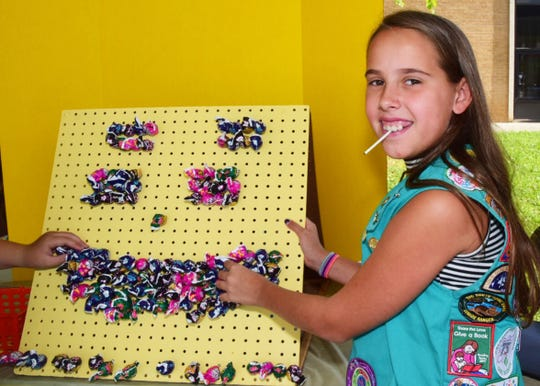Ava Berkheimer, 10, with Girl Scout Troop 20034 sets up a display of suckers at one of the many games featured in the Children's Midway at the 2018 Karns Community Fair on July 28.