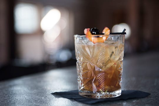 A peach Old-Fashioned, which includes whiskey, honey liqueur and peach bitters, sits on the bar at the Walnut Kitchen in Maryville on Thursday, July 26, 2018.