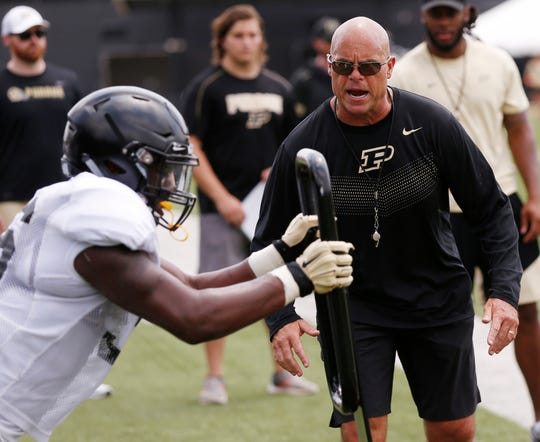 Linebackers coach and co-defensive coordinator Nick Holt shouts instructions as linebackers hit the blocking sled during football practice Friday, August 3, 2018, at Purdue.