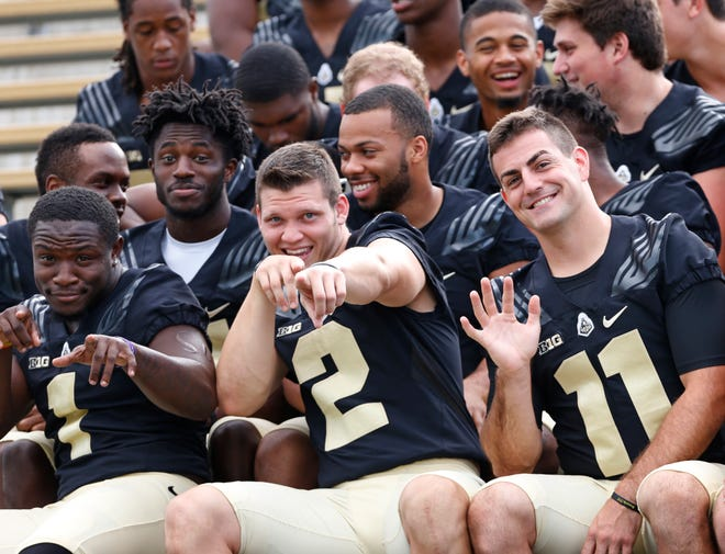 The bond between Purdue quarterbacks Elijah Sindelar (2) and David Blough (11) is no act teammates say. The pair clowned for the cameras with running back D.J. Knox, left, during Purdue football media day earlier this month.