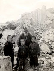 This photograph shows Jim Bowes with three Japanese young boys in Hiroshima about one year after the United States detonated an atomic bomb over the city. Bowes said his unit's interrupter said the boys were in the city with their mother looking to see what was left of their old neighborhood. The boys and their mother were in the countryside when the bomb detonated.