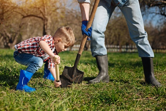 Young child digging in the dirt.