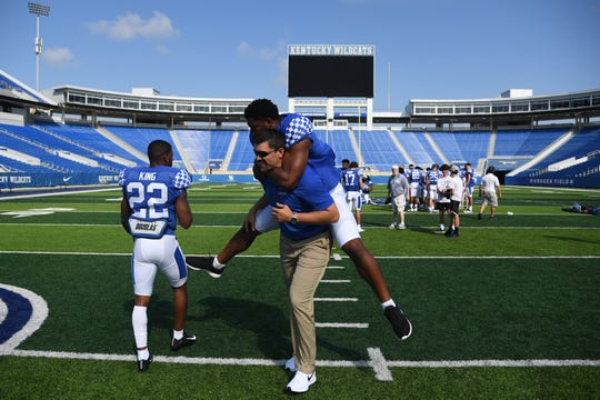 Josh Allen jokes around and gets a ride from linebackers coach Brad White during UK's media day session in August 2018.
