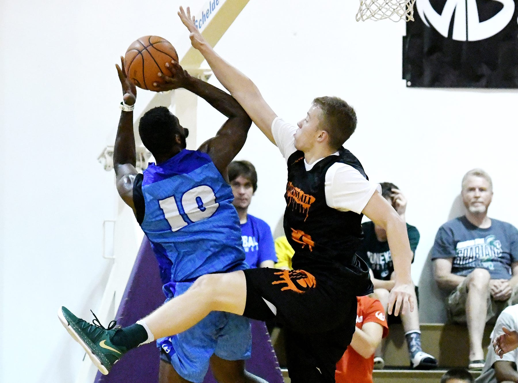 Team Splatter's Thomas Kithier, right, guards Team Definition's Gregory Roy on Thursday, Aug. 2, 2018, during the Moneyball Pro-Am summer basketball league championship game at Aim High in Dimondale. Team Definition won the game 99-83.
