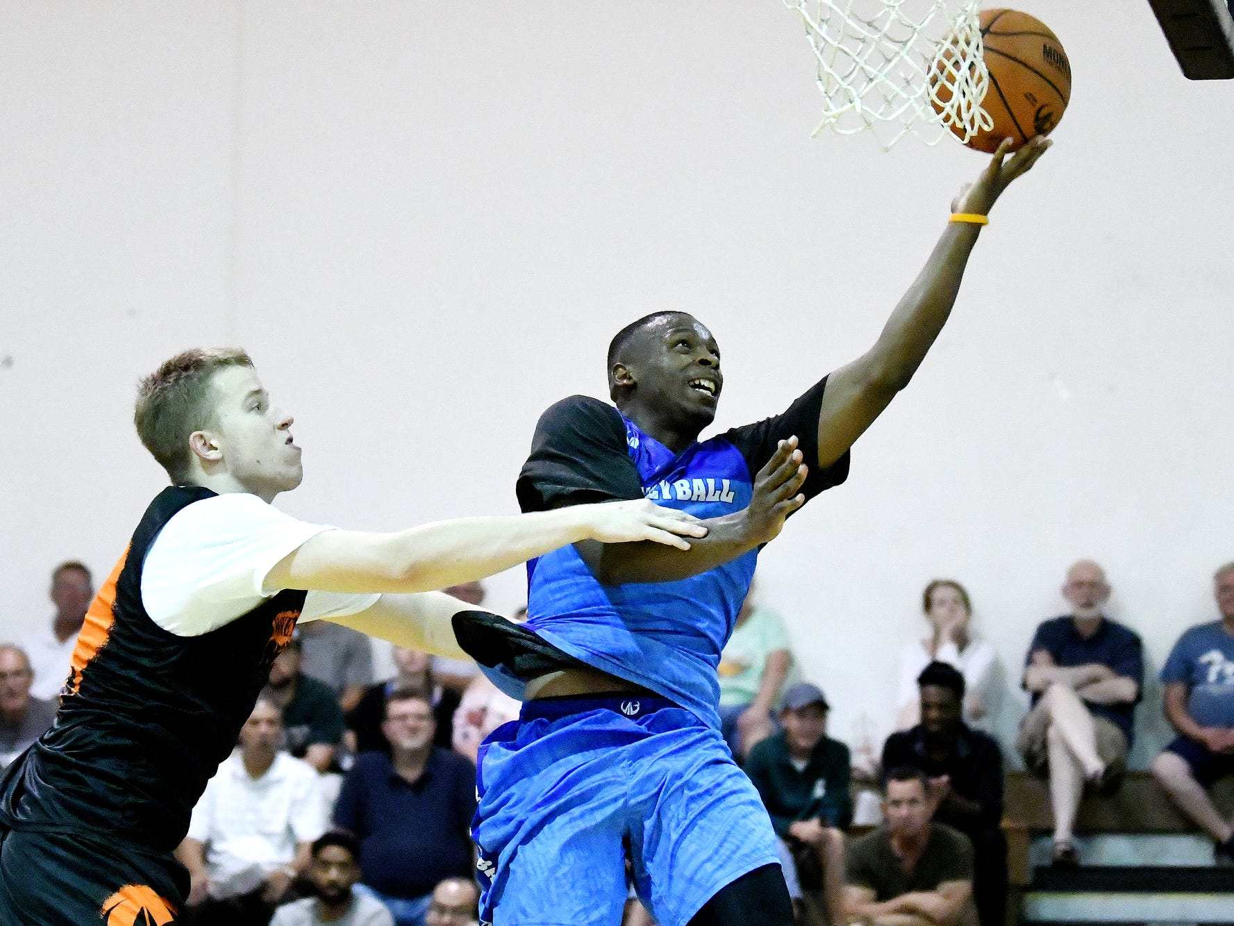 Team Definition's Clavontae Brown, right, is fouled by Team Splatter's Thomas Kithier on Thursday, Aug. 2, 2018, during the Moneyball Pro-Am summer basketball league championship game at Aim High in Dimondale. Team Definition won the game 99-83.
