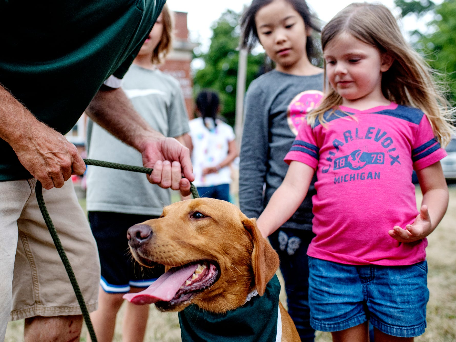 Children line up to meet Zeke the Wonderdog IV after a performance at Play in the Park on Tuesday, July 31, 2018, at Valley Court Park in East Lansing.