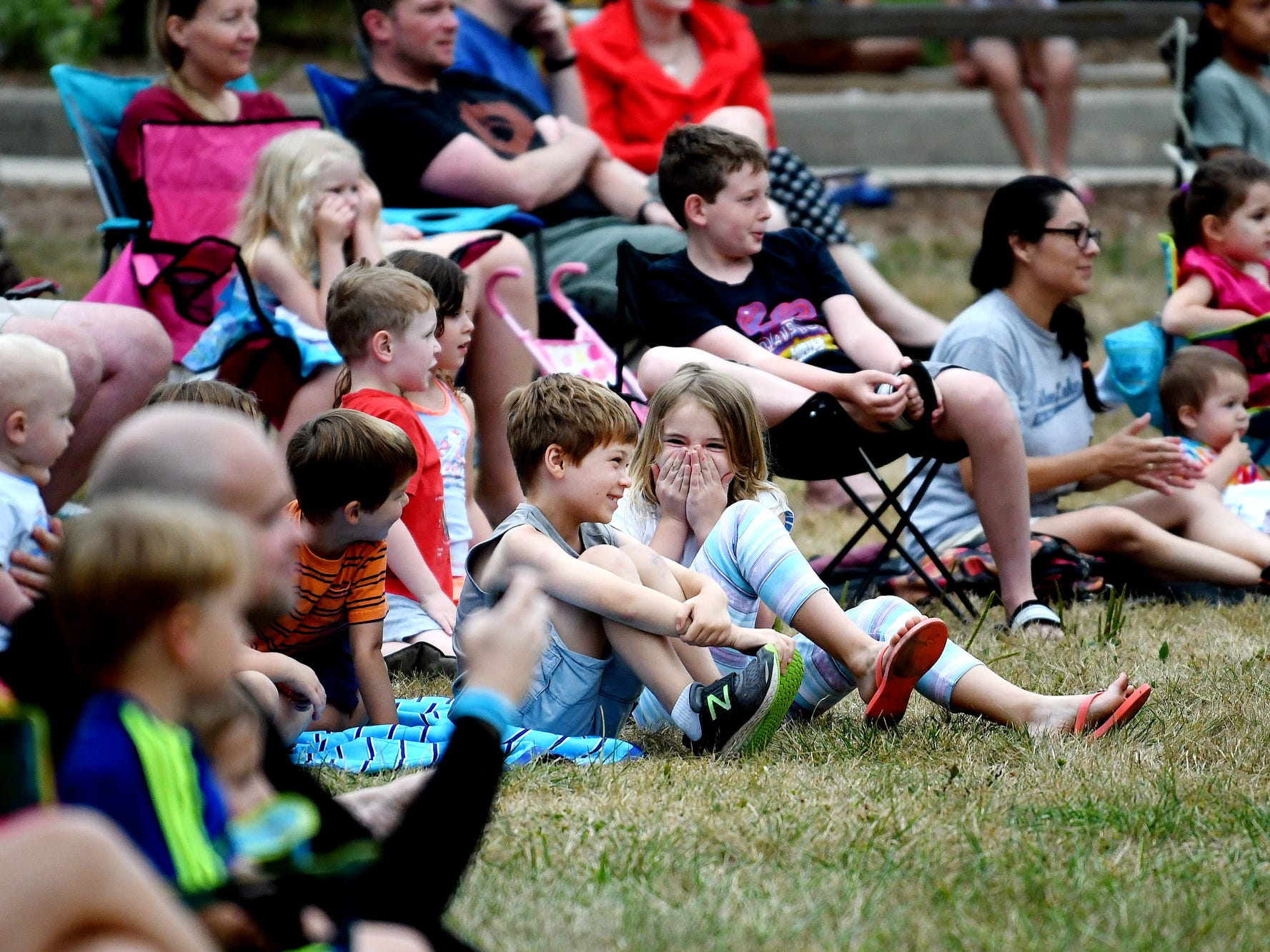 Children and adults watch as Zeke the Wonderdog IV performs with other dogs during Play in the Park on Tuesday, July 31, 2018, at Valley Court Park in East Lansing.
