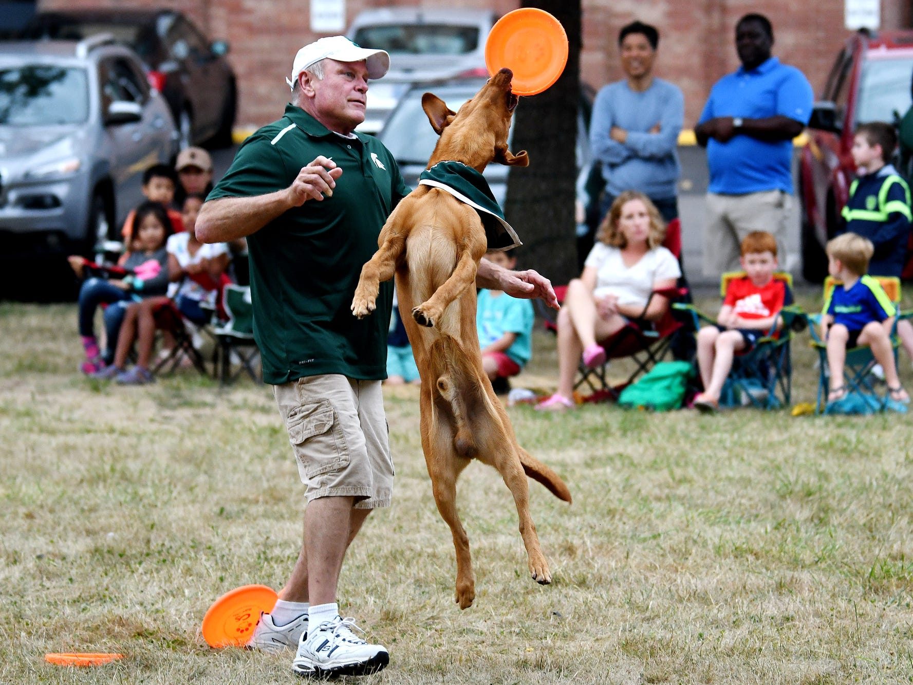 Zeke the Wonderdog IV catches a flying disc in his mouth as his caretaker Jim Foley watches during Play in the Park on Tuesday, July 31, 2018, at Valley Court Park in East Lansing.
